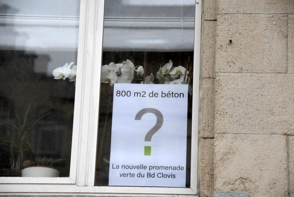 Fenêtre-avec-affiches-contre-le-béton-et-fleurs